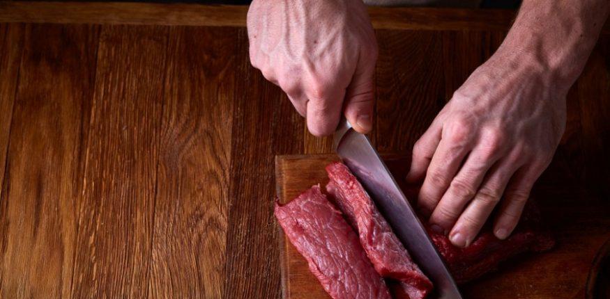 Un homme coupe un morceau de viande